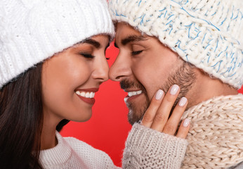 Lovely young couple in knitted hats on red background, closeup. Christmas celebration