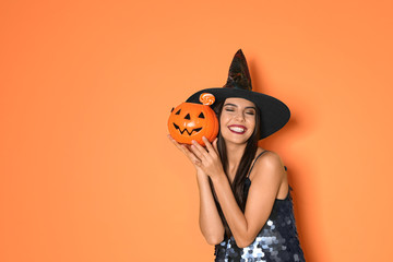 Beautiful woman wearing witch costume with Jack O'Lantern candy container for Halloween party on...