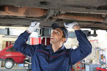 Male mechanic repairing car in service center