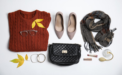 Fototapete - Warm clothes, autumn leaves and accessories on white background, top view