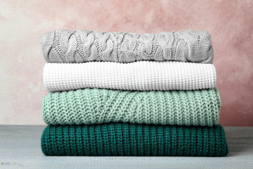 Fototapete - Stack of warm clothes on grey wooden table against light background. Autumn season