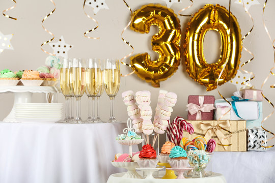 Dessert table in room decorated with golden balloons for 30 year birthday party