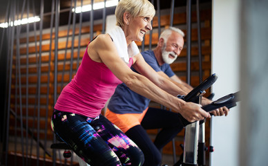 Vital mature couple exercising in the gym. Wall mural