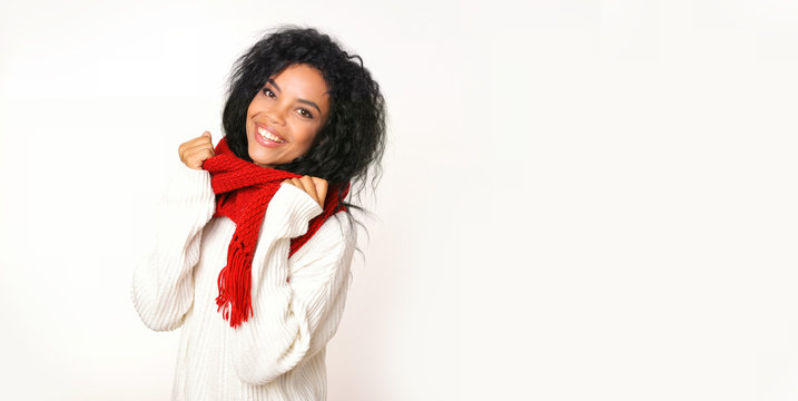 Creature comforts. Front portrait of young smiley African ethnic girl, who is wearing a snow-white sweater and red knitted scarf and adjusting it with her hands.