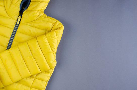 Yellow kids winter jacket composition on yellow background.