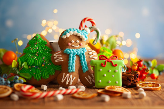 Christmas gingerbread cookies with Christmas decorations on wooden background.