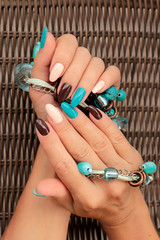 Oval multicolored manicure on a woman's nails.Nail design with turquoise, brown, light beige nail Polish.