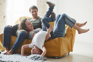 Having leisure. Happy family have fun on the yellow sofa in the living room of their new house