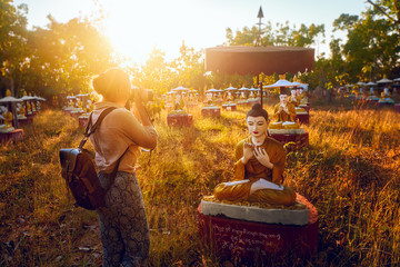 woman traveler takes pictures and enjoys beautiful statues of Buddhas near Monwa (Myanmar) Thanboddhay Pai at sunset.