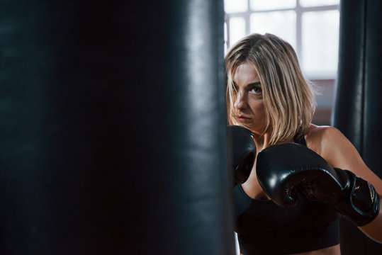 Anger and energy. Female boxer is punching the bag. Blonde have exercise in the gym