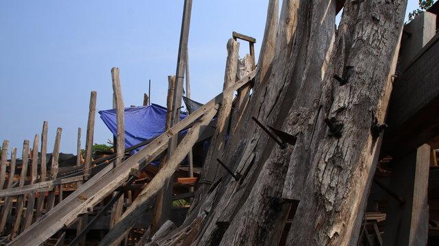 Timber shipbuilder working while working at a shipyard, Batang Indonesia,