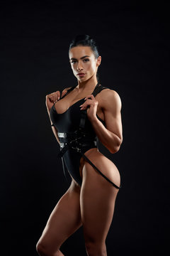 Gorgeous woman in black bodysuit and leather bandage.