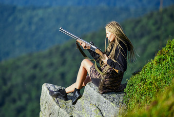 Hunting season. Hunter mountains landscape background. Sexy warrior. Woman attractive long hair pretty face hold rifle for hunting. Amazon girl sit on cliff prepare gun for hunting. Aiming concept