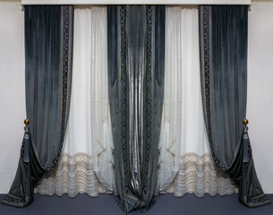 Modern interior design in black and white colors. Straight velvet curtains and translucent tulle with a geometric pattern