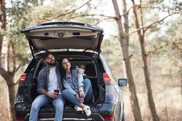 Front view. Sitting on rear part of automobile. Enjoying the nature. Couple have arrived to the forest on their brand new black car