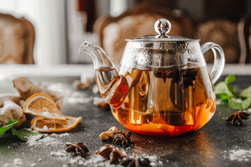 Leaf tea in a glass teapot on the black table