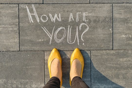 How are you written on gray sidewalk with women legs, top view