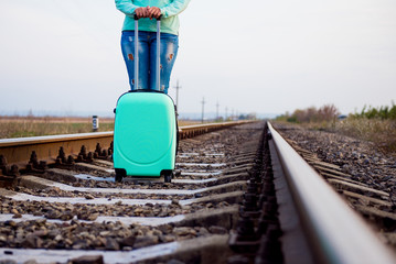 Girl with a suitcase by the railway. Turquoise suitcase. Girl tourist with a suitcase on a railway platform. Autumn train ride. Railway in the fall.