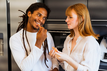 Woman in a white shirt and black boy with dreadlocks in a kitchen eating carrots and talking to each other