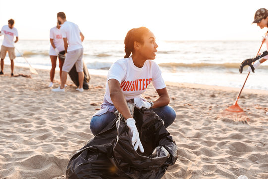 Image of volunteers worker cleaning beach from plastic with trash bags