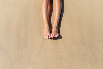 Top view of naked tanned women's feet in the sand on the beach, point of view of feet in the sand on the ocean, summer background-image, rest on the ocean beach, feet on the sea sand-image Wall mural