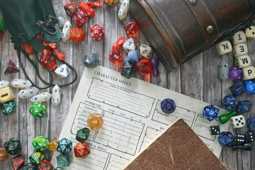 Tabletop roleplaying flat lay with colorful RPG and game dices,  character sheet, rule book and treasure chest on wooden desk