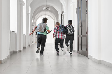 Group of schoolboys with school backpacks running.
