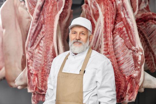 Professional butcher in uniform standing near pork carcasses