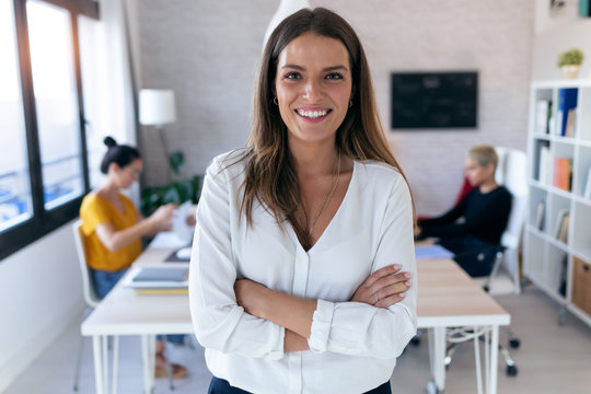 Pretty young businesswoman looking at camera. In the background, her colleagues working in the office.