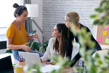 Three modern female entrepreneurs who talk about new ideas for to next work in a joint workspace.