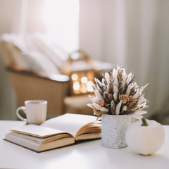 Autumn still life. Coffee cup, flowers, book and pumpkin. Hygge lifestyle, cozy autumn mood. Flat lay, Happy thanksgiving