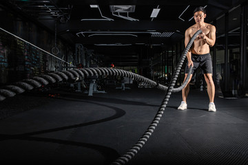 Handsome muscular man is doing battle rope exercise while working out in gym