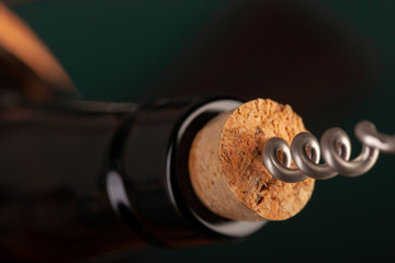 Opening a wine bottle with a cork screw in a restaurant