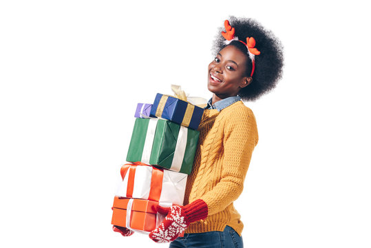 happy african american girl in christmas antlers holding stack of presents, isolated on white