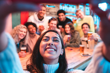 Happy friends taking a group selfie at pub