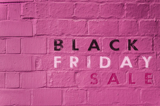 """""""Black Friday Sale"""" text on a pink brick wall"""