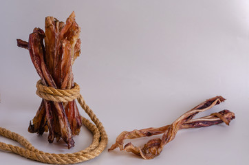Dried beef tendon on a light background. Chewing treats for pets. Close-up. Eye level shooting. Side view. Free space for text. The horizontal version of the picture.