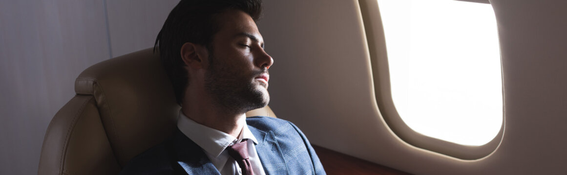 handsome businessman sleeping in plane during business trip