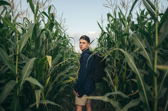 Fashionable photo of attractive young man with backpack and casual clothes standing in corn field and posing at camera. Portrait of stylish tourist guy in corn field.