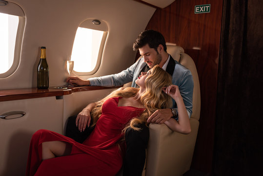 sensual couple with champagne sitting in airplane