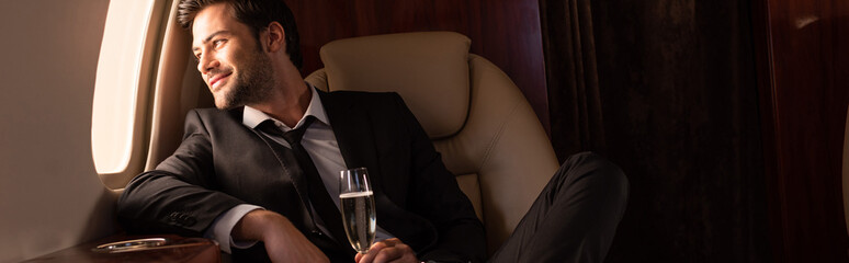 handsome cheerful man holding glass of champagne in plane
