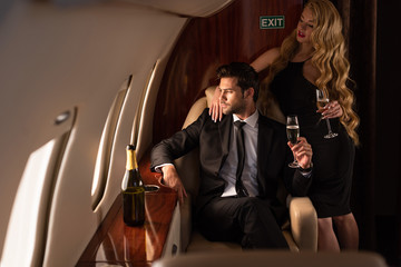 elegant fashionable with champagne traveling in plane