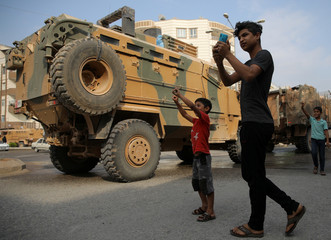 Man takes pictures as Turkish military vehicles drive on a street in the Turkish border town of Akcakale