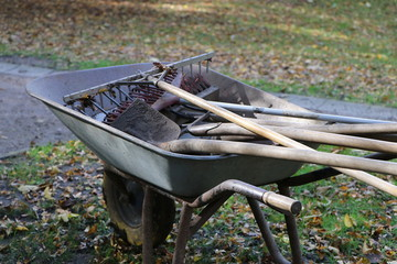 wheelbarrow with fork and spade in autumn