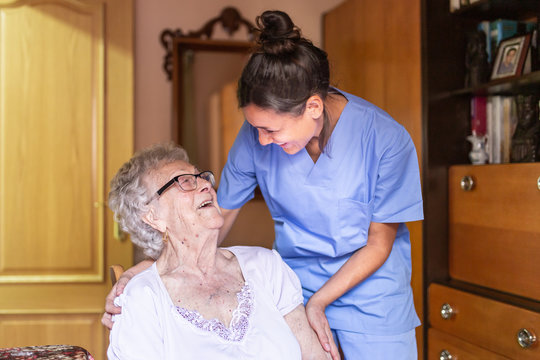 Happy Senior woman laughing. with her caregiver at home. Senior home care concept.