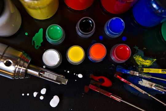 Colorful tattoo ink in caps capswith tattoo machine, ink bottles, used tattoo needles and ink splotcheses
