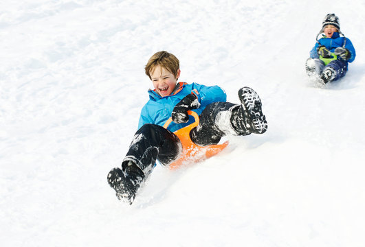 Cute young boys sledging and having fun in the snow