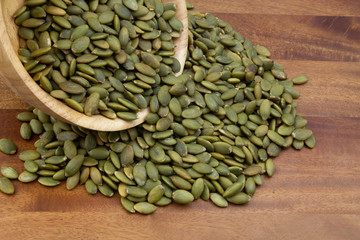 Green pumpkin seeds in wooden bowl and on wooden table