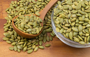 Pumpkin seeds with wooden spoon and glass bowl