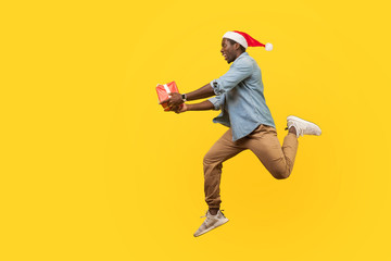 Full length side view of joyous handsome young man in santa hat and casual denim shirt jumping or running with christmas gift box, hurry for sales. indoor studio shot isolated on yellow background Wall mural